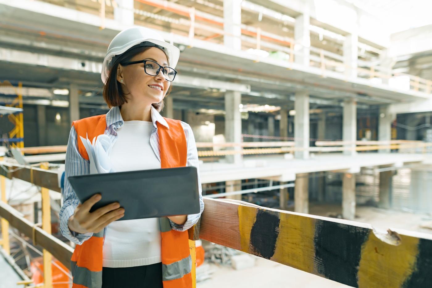 Portrait of mature architect woman at a construction site. Building, development, teamwork and people concept.