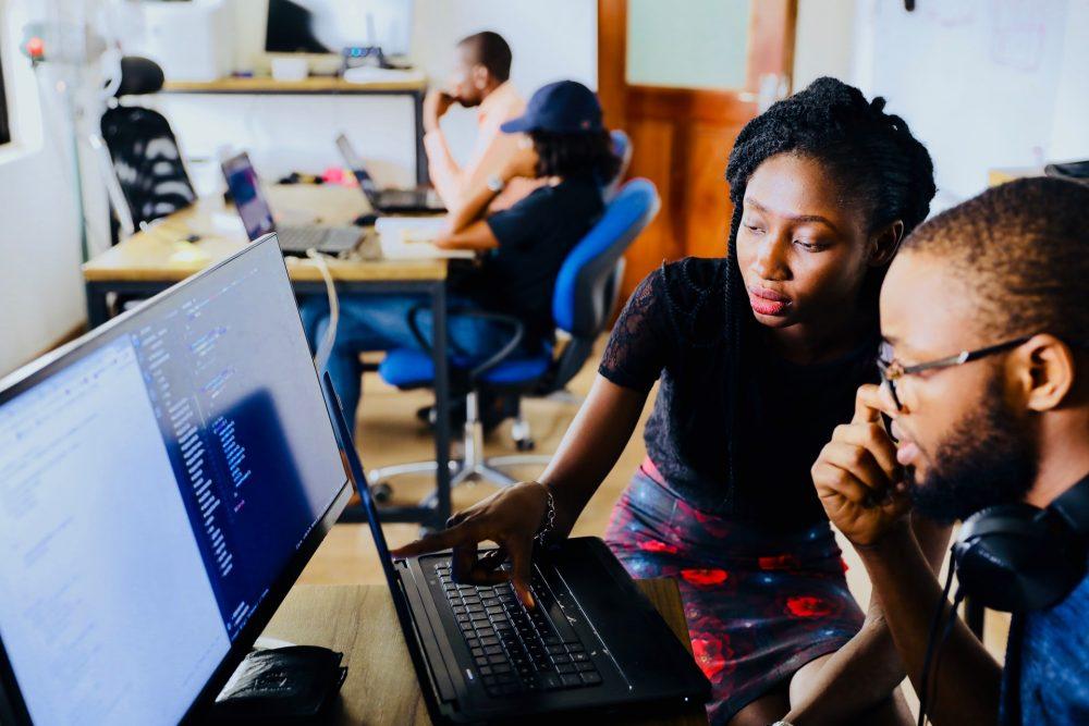 man and woman discussing tech, women in tech, computers, code, development