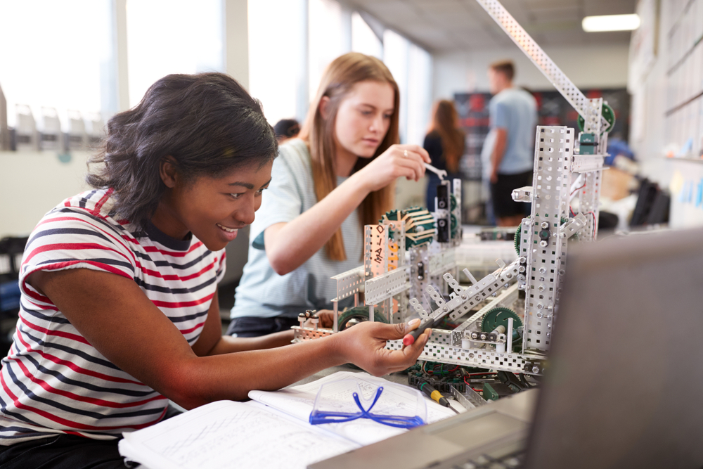 Two Female College Students Building Machine In Science Robotics Or Engineering Class, International Women in Engineering Day