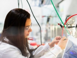 woman wearing a white lab coat working on an engineering project, International Women in Engineering Day
