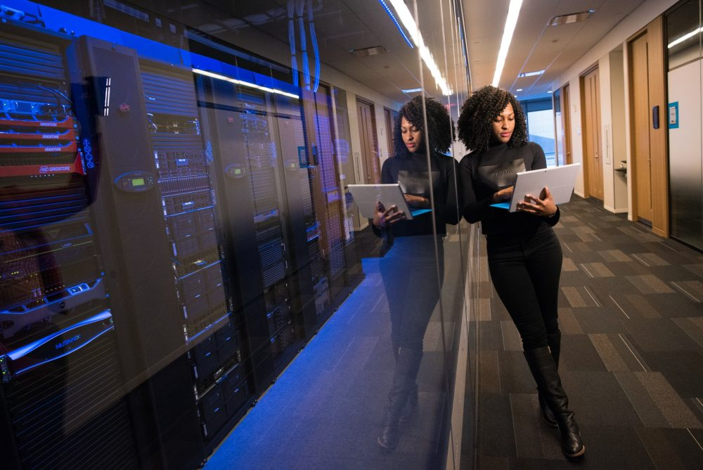 black woman working on computer in the hallway, diversity, SysAdmin Day, SysAdmins