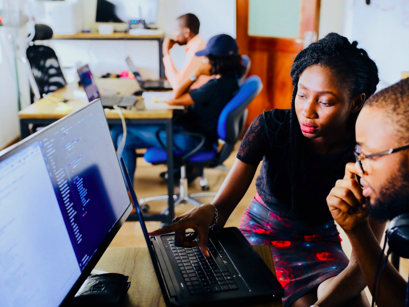 woman and man looking at a computer screen with coding, carving a career in  tech - WeAreTechWomen - Supporting Women in Technology