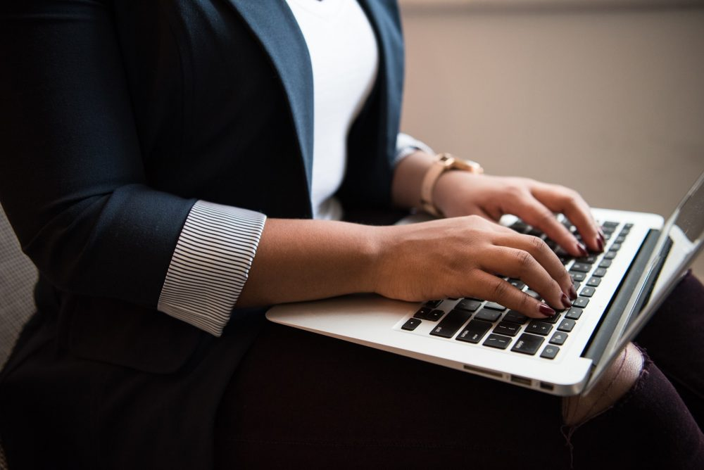 woman in tech working on a laptop, online