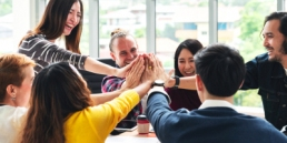 group of young multiethnic diverse people gesture hand high five, laughing and smiling together in brainstorm meeting at office, company culture