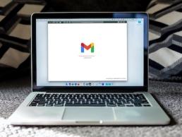 macbook pro on black background displaying Gmail, phishing emails