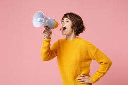 woman with a megaphone shouting to get her voice heard, female leader