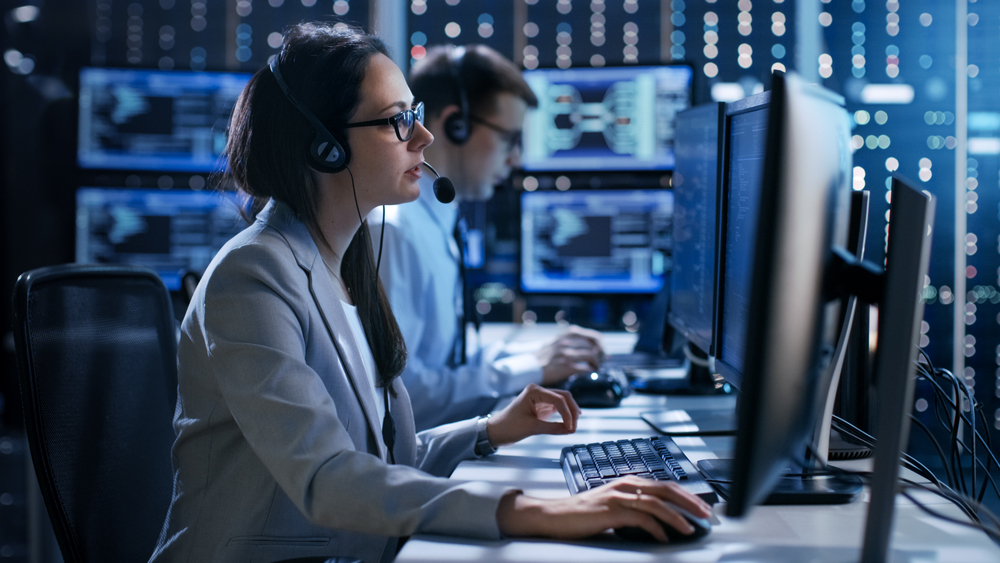 Female working in a Technical Support Team Gives Instructions with the Help of the Headsets. In the Background People Working and Monitors Show Various Information, SysAdmin Day