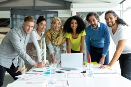 Front view of diverse business people looking at camera while working together at conference room in a modern office